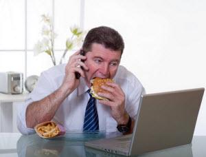Мужчина ест фаст-фуд
